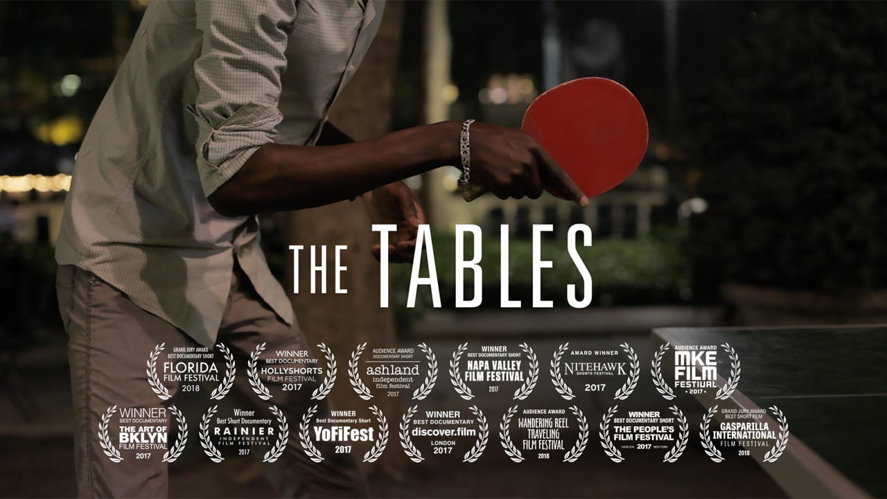 "A Black person holding a red table tennis paddle with the title ""The Tables"""
